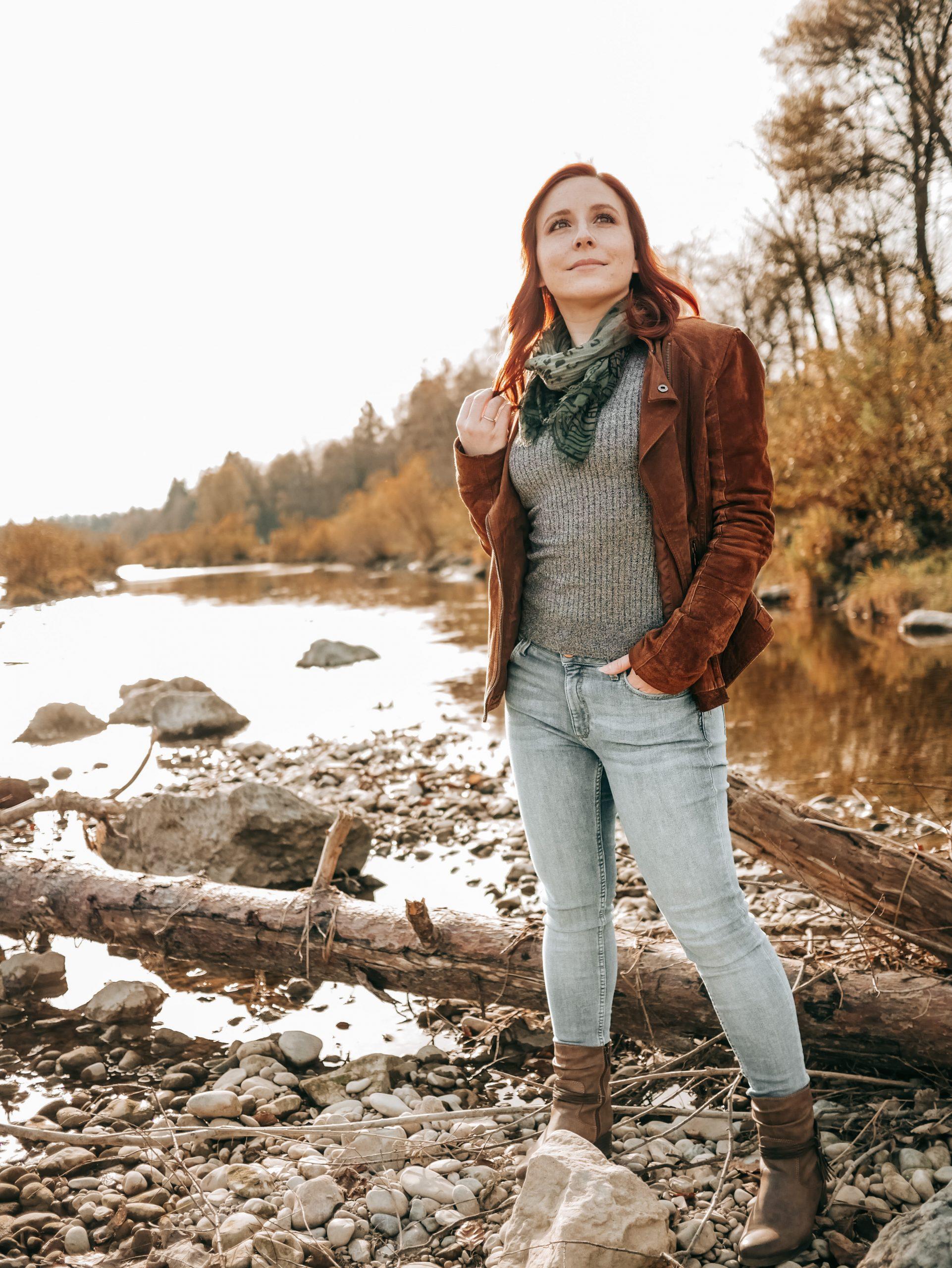 Frau steht am Wasser vor einem Baumstamm und blickt hoffnungsvoll nach oben.