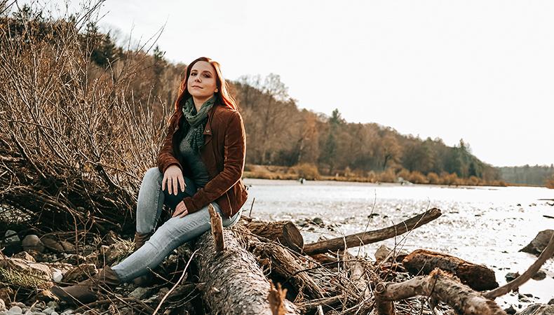 Frau sitzt auf Baumstamm am Wasser